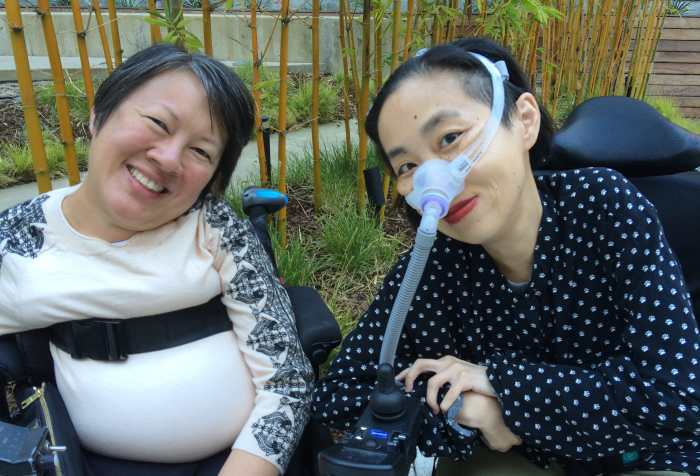 On the left is Ing Wong-Ward, a Chinese Canadian disabled woman with short black hair and a cream top with black decorative print on the sleeves. She is in a wheelchair with a belt across her chest. On the right is Alice Wong, A Chinese American disabled woman with short black hair and a black shirt with small white cat paw prints. She is in a wheelchair and wearing a mask over her nose attached to a tube for her ventilator.