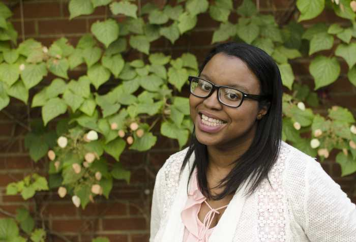 Black woman with black hair and black glasses is wearing a white shirt and smiling in front of a green flowered wall. Photo credit: Reid Beels