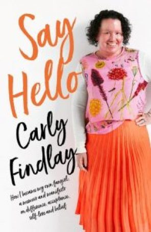 "Book cover featuring woman with red face and short dark curly hair, smiling. She's wearing a pink floral top and bright orange skirt. Her hand is on her hip. Curly orange text reads ""Say Hello"", and black text reads ""Carly Findlay How I became the fangirl of my own story - a memoir and manifesto on difference, acceptance, self love and belief."""