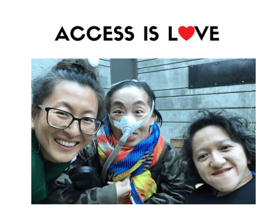 """Photo of 3 disabled Asian Americans, Mia Mingus, Alice Wong and Sandy Ho (from left to right). Mia is wearing glasses and large hoop earrings. Alice is wearing a brightly colored scarf and an army-camouflage-print jacket. She is wearing a mask over her nose with a tube for her Bi-Pap machine. Sandy has wavy short hair and is wearing a black sweater. Behind them is a concrete wall with a door. On the top against a white background in black text: """"ACCESS IS LOVE"""" in white. The """"O"""" in """"LOVE"""" is a red heart."""