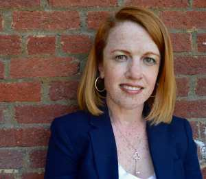 A photo of a red-haired and freckled woman wearing a blue blazer and standing in front of a red brick wall
