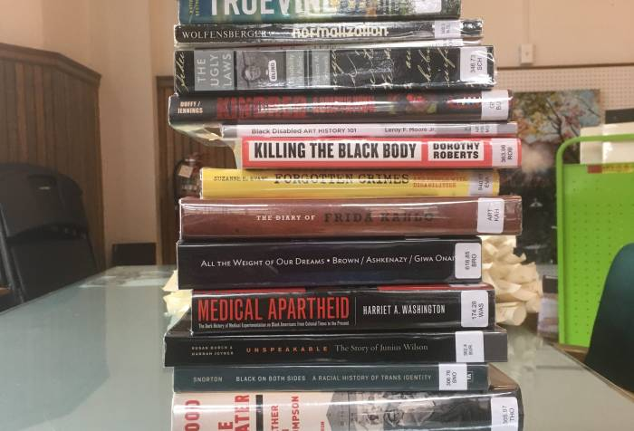 A stack of 17 library books lying horizontally. Text on the spines of the books from top to bottom: The Girl with All the Gifts, Disability and Difference in Global Contexts, Truevine, Normalization, The Ugly Laws, Kindred, Black Disabled Art History 101, Killing the Black Body, Forgotten Crimes, The Diary of Frida Kahlo, All the Weight of Our Dreams, Medical Apartheid, Unspeakable: The Story of Junnius Wilson, Black on Both Sides: A Racial History of Trans Identity, Blood in the Water, Sick from Freedom, Thinking Class