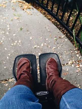 A sidewalk with bits of leaves on the ground. In the foreground, a pair of legs with denim jeans wearing soft brown leather boot socks. The feet are resting on a wheelchair's footrests.