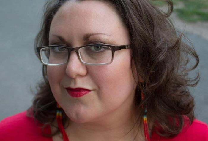 Close up of a light complexion, Two Spirit femme with black glasses, green eyes, shoulder length brown hair, Native style beaded dangling earrings, with bright red lips and a red shirt. In the foreground is a paved path and grass.