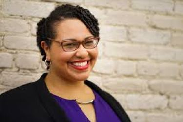 Medium shot of Dr. Sami Schalk. She is a light-skinned black woman with short curly hair and brown glasses. She is smiling to the camera in front of an off-white painted brick wall. She is wearing a black velvet jacket over a purple dress, red lipstick, and silver hoop earrings. Photo by Smoketree Photography of Madison, WI.
