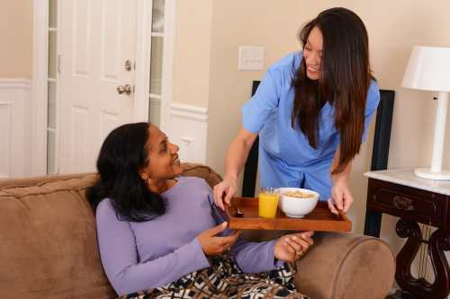 Photo of a Black person sitting on a couch with a blanket on their lap receiving a tray with a glass of orange juice and a bowl of cereal from a Latinx person in blue scrubs.