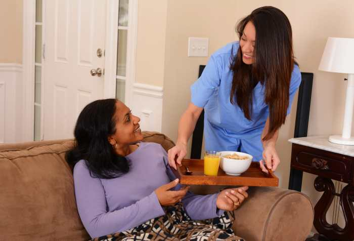 Photo of a person sitting on a couch with a blanket on their lap receiving a tray with a glass of orange juice and a bowl of cereal from a person in blue scrubs.
