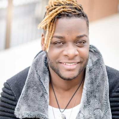 Picture of a Black man with blonde dreadlocks smiling at camera wearing a black ribbed sweater jacket with grey fur collar, white t-shirt and two silver necklaces. Photo credit: RJ Patel