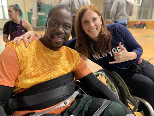 Photo of Daryl Chill Mitchell [left] a Black man in a chair designed for wheelchair rugby next to Katherine Beattie, a white woman in a manual wheelchair with her arm around his shoulder. Photo courtesy of Katherine Beattie.