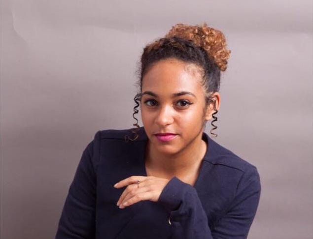 Cropped photo of Kalia Douglas-Micallef, a young Black disabled woman. She is sitting and wearing a navy blue top and dark gray pants with a geometric pattern. Her curly brown hair is tied up with ringlets of hair at both sides of her face. Her legs are crossed and her eyes are staring straight at the camera. Photo credit: Sean Anthony