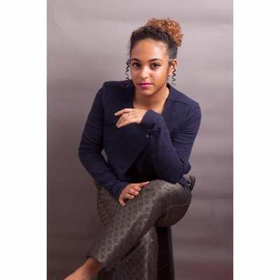 Photo of Kalia Douglas-Micallef, a young Black disabled woman. She is sitting and wearing a navy blue top and dark gray pants with a geometric pattern. Her curly brown hair is tied up with ringlets of hair at both sides of her face. Her legs are crossed and her eyes are staring straight at the camera. Photo credit: Sean Anthony