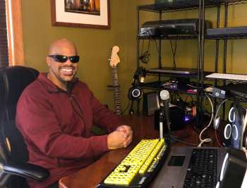 Thomas Reid an African American man with a clean shaven head and goatee in shades smiles at the camera while seated at a desk. The desk holds a laptop and other equipment including an audio mixer and microphone. A framed picture of the original World trade Center hangs on the wall above a black Fender electric guitar.