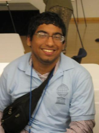Hamza Jaka, a brown American Pakistani man, smiles up at the camera. He is wearing glasses, a blue UNESCO Chair Institute shirt, and a fanny pack along with lanyard.
