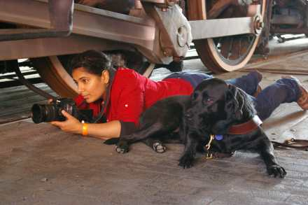 An Arab-American woman with dark hair in jeans and a red shirt on the floor holding a camera about to take a photo. Next to her lying on the ground is a black Labrador guide dog.