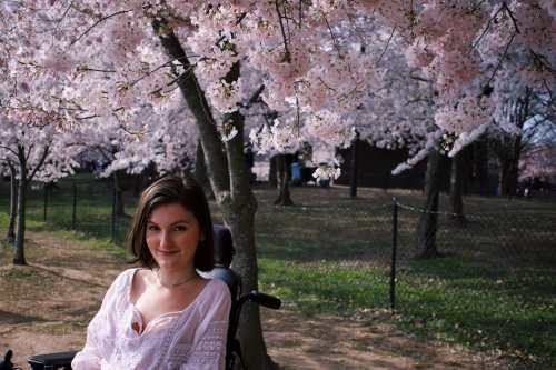 A young white woman with chin-length brown hair smiles at the camera. She wears a white shirt and sits in a black motorized wheelchair. Behind her are several blooming cherry blossom trees.