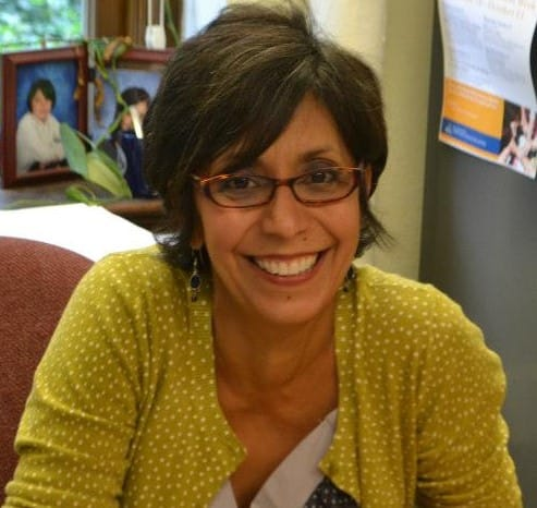 Latina woman with short black and grey hair, wearing brown-rimmed glasses and yellow sweater with white polka dots smiles widely at her desk.
