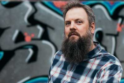 A white male about 40 years old with a long beard and greying hair looks at the camera. He wears a blue and red plaid shirt. Behind him is a mural silver, pink, and blue graffiti lettering.