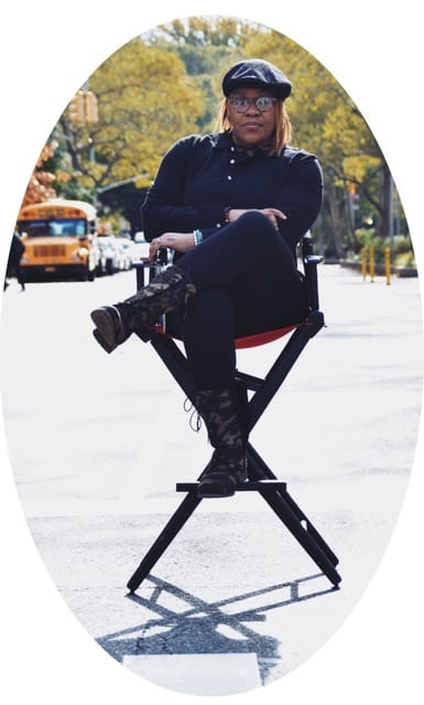 Oval photo of Jade Bryan, a Black Deaf woman sitting in a director's chair outdoors with trees and parked cars behind her. She is wearing all black, and a black beret and glasses. Her left leg is crossed over her right, both arms folded.