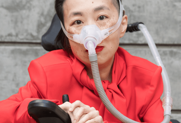 Photo of an Asian American woman in a power chair. She is wearing an orange-red jacket and black pants. She is wearing a mask over her nose attached to a gray tube and bright red lip color. Her hands are resting over her joystick. Photo credit: Eddie Hernandez Photography