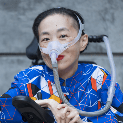 Photo of an Asian American woman in a power chair. She is wearing a blue shirt with a geometric pattern with orange, black, white, and yellow lines and cubes. She is wearing a mask over her nose attached to a gray tube and bright red lip color. She is smiling at the camera. Photo credit: Eddie Hernandez Photography