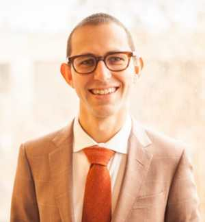 Sean Betouliere – a white man in his mid-30s with close-cut hair, thick-framed glasses, a brown suit, and an orange tie—smiles for the camera