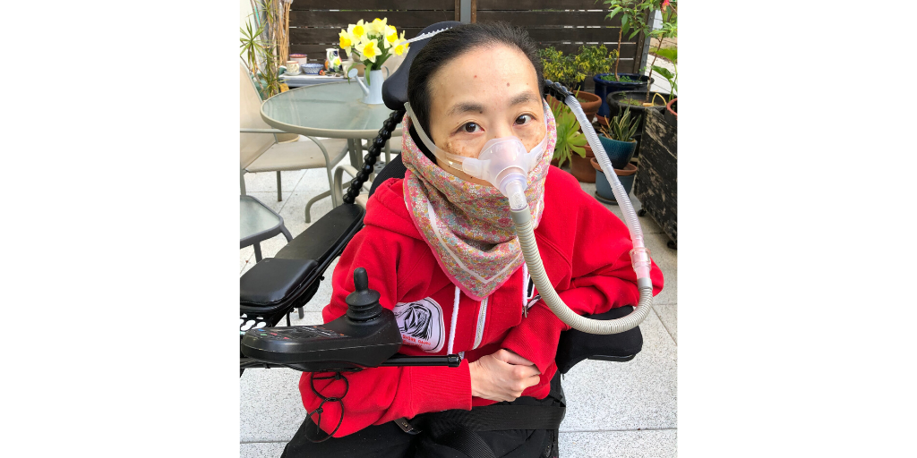 Asian American woman in a power chair sitting at a patio with a red hoodie and a floral print handkerchief around her mouth. She's wearing a mask over her nose attached to a gray tube.