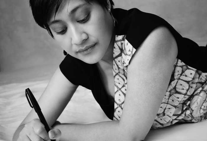 Black and white photo of an Indonesian woman with short hair, earrings, and a patterned dress, lying down on her front, pen in hand, ready to write. Pic credit: Derrick Kakembo.