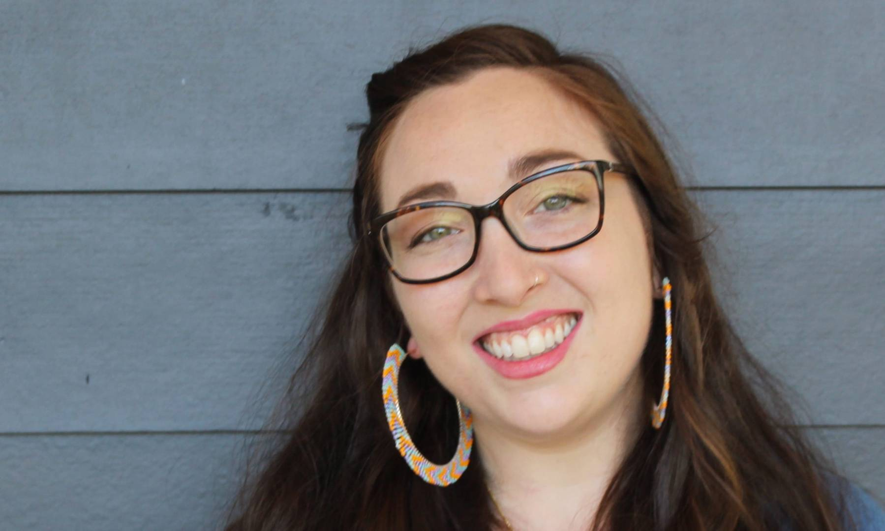 A pale white woman with brown hair, green eyes, and tortoiseshell glasses leans against the blue siding of a house, looking at the camera and smiling. She is in a blue, denim shirt and has on large blue and yellow beaded hoop earrings and a black and gold Magen David necklace.