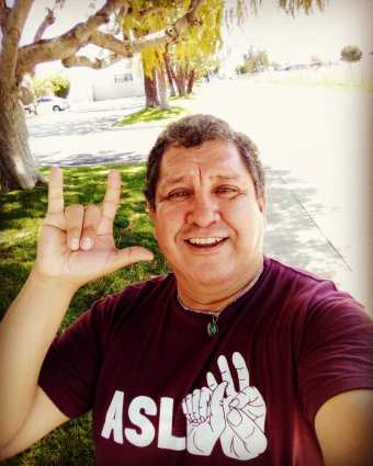 "Photo of Hector M. Ramirez, a Latino Chiricahua Apache man wearing a maroon t-shirt that says ASL with 3 illustrations of hands spelling the letters a-s-l. His right hand is showing the sign, ""I love you"" in American Sign Language."