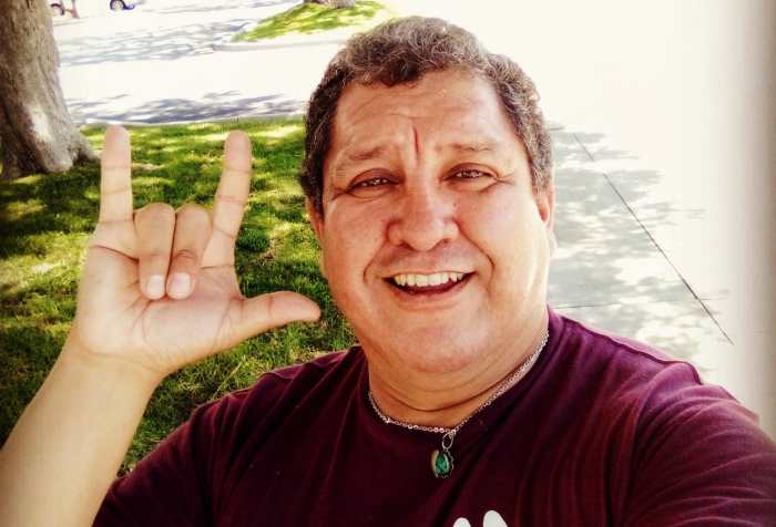 "Photo of Héctor M. Ramírez, a Latino Chiricahua Apache man wearing a maroon t-shirt that says ASL with 2 illustrations of hands spelling 'a' and 'f' as in af meaning ""as fuck"". His right hand is showing the sign, ""I love you"" in American Sign Language."