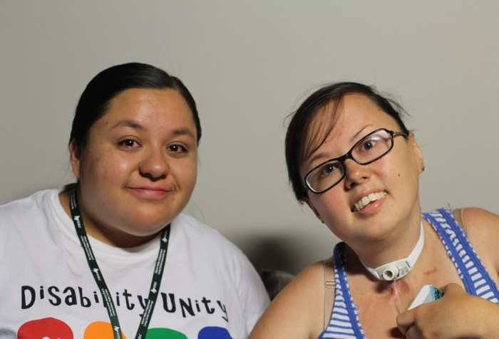 [Left] Dolores is a fat brown femme with a round face. She smiles without showering teeth. Their black hair is pulled back. [Right] Stacey is a mixed race Korean and white queer person wearing a blue-and white striped tank top and her trach can be seen.