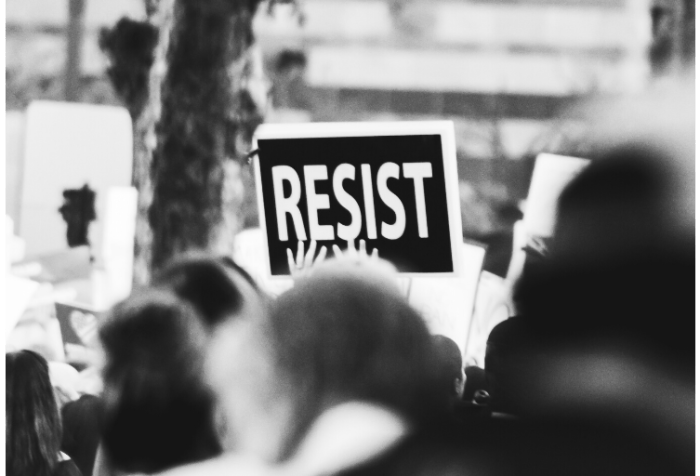 Black and white photo of an outdoor protest with one sign that says RESIST in white letters against a black piece of cardboard