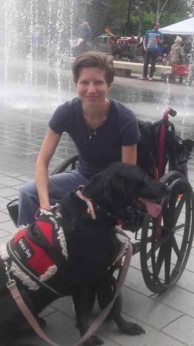 Amanda Siebe, a white woman in a wheelchair and her service dog, Dobby.