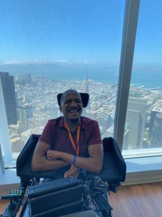 I am in a red polo shirt and jeans and a orange lanyard is around my neck. I am sitting in my black and red Permobile wheelchair. My iPad and a black scarf is on my tray. I am in the top of the Salesforce Tower and behind me is a view of the San Francisco skyline.