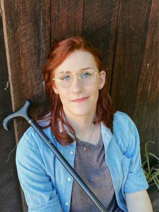 A white trans woman sitting in front of a wooden shed. She has shoulder-length red hair and a scar cutting through one eyebrow. There is a black cane propped against her shoulder. She is dressed in a gray t-shirt and a blue chambray button-up. She is wearing gold wire-frame glasses and has silver rings in her ear lobes and septum. There is a gold ring on a chain around her neck.