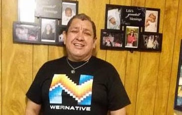 "Picture of Hector standing in the hallway of his house. The walls and floors are wooden and there are some pictures of his family on the wall. He is standing and is wearing a T-shirt that reads WeRNative that has an native patterns. He is wearing dark blue jeans and great Crocks. His hands are in his pant pockets and he is wearing a lime green bracelet that reads ""Each Mind Matters"". He is smiling at the camera and is wearing a turquoise and silver pendant on a small chain around his neck."
