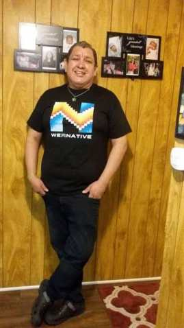 """Picture of Hector standing in the hallway of his house. The walls and floors are wooden and there are some pictures of his family on the wall. He is standing and is wearing a T-shirt that reads WeRNative that has an native patterns. He is wearing dark blue jeans and great Crocks. His hands are in his pant pockets and he is wearing a lime green bracelet that reads """"Each Mind Matters"""". He is smiling at the camera and is wearing a turquoise and silver pendant on a small chain around his neck."""