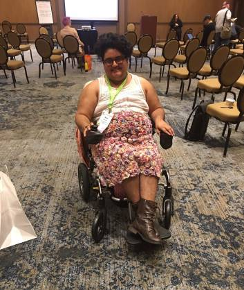 A south asian person poses in a Jazzy Passport folding power chair. He has on brown lace up boots, a colorful floral skirt, and a white lace top. He has a conference badge. He is smiling.