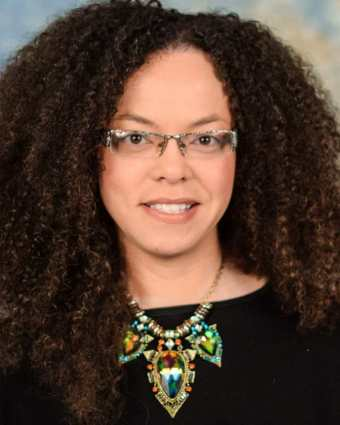 Headshot of a light complected African American woman, late thirties, with curly brown hair and glasses. She is wearing a black top and a large statement necklace