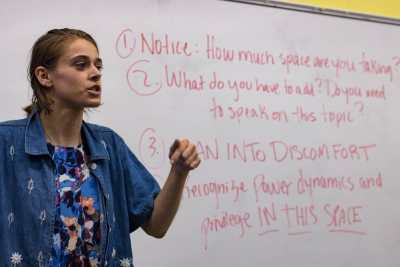 "A white femme-presenting person with dark blonde hair stands in front of a white board with a blue floral shirt and a jean jacket. The white board has red text on it, which states: ""1. Notice: How much space are you taking? 2. What do you have to add? Do you need to speak on this topic? 3. Lean into discomfort. 4. Recognize power dynamics and privilege in this space."""