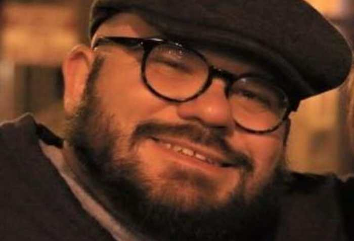 White, cis man with dwarfism smiles at the camera. He has a shaved head and short beard andis wearing dark rimmed glasses, a dark driver's cap, and dark cardigan over a light t-shirt.