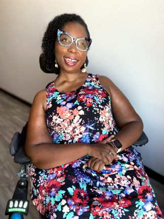 Black woman in a power chair wearing a sleeveless dress with a floral print in bright colors. Her eyeglass frame is cat-eye shaped black and teal. She is smiling and looking slightly away from the camera.