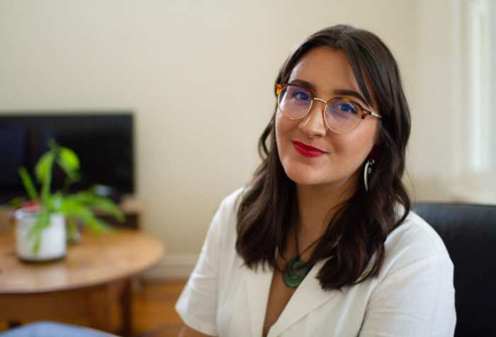 Photo of Kera Sherwood-O'Regan, an Indigenous Māori woman with light olive skin and long brown hair, sitting in her living room. She is wearing a white collared jumpsuit, vintage style tortoiseshell glasses, Haus of Dizzy love heart earrings, and red lipstick. She wears a Māori pounamu greenstone pendant around her neck, and she is smiling slightly at the camera. There is a green houseplant and wooden furniture in the background.