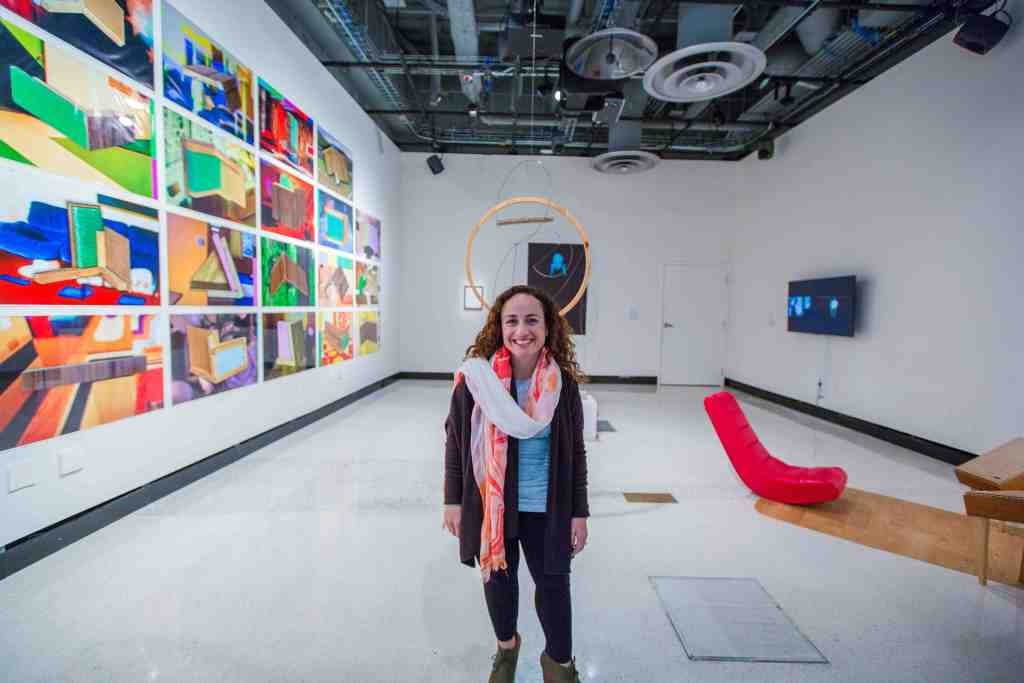 A short-statured woman with long brown curly hair and brown eyes stands in the middle of a white cube gallery space, smiling at the camera. She is wearing red lipstick to match the red and white scarf wrapped around her neck. On every wall of the gallery space hangs contemporary art that includes brightly-colored photographs of abstract shapes, a round wooden ring hanging from the ceiling, a black and white video installation of a sign language interpreter and a low-lying red lounge chair on a mat. The ceiling is exposed so all the beams, wiring and fan ducts are visible.