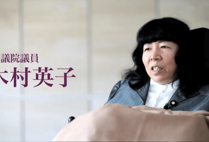 Graphic showing a picture of Eiko Kimura, a Japanese woman in a wheelchair. She has long black hair and wearing a navy jacket and a white shirt. A beige blanket is on her lap. On the right in Japanese 参議院議員 木村英子is text translated: Upper House Member (or member of the House of Councillors), Kimura Eiko.
