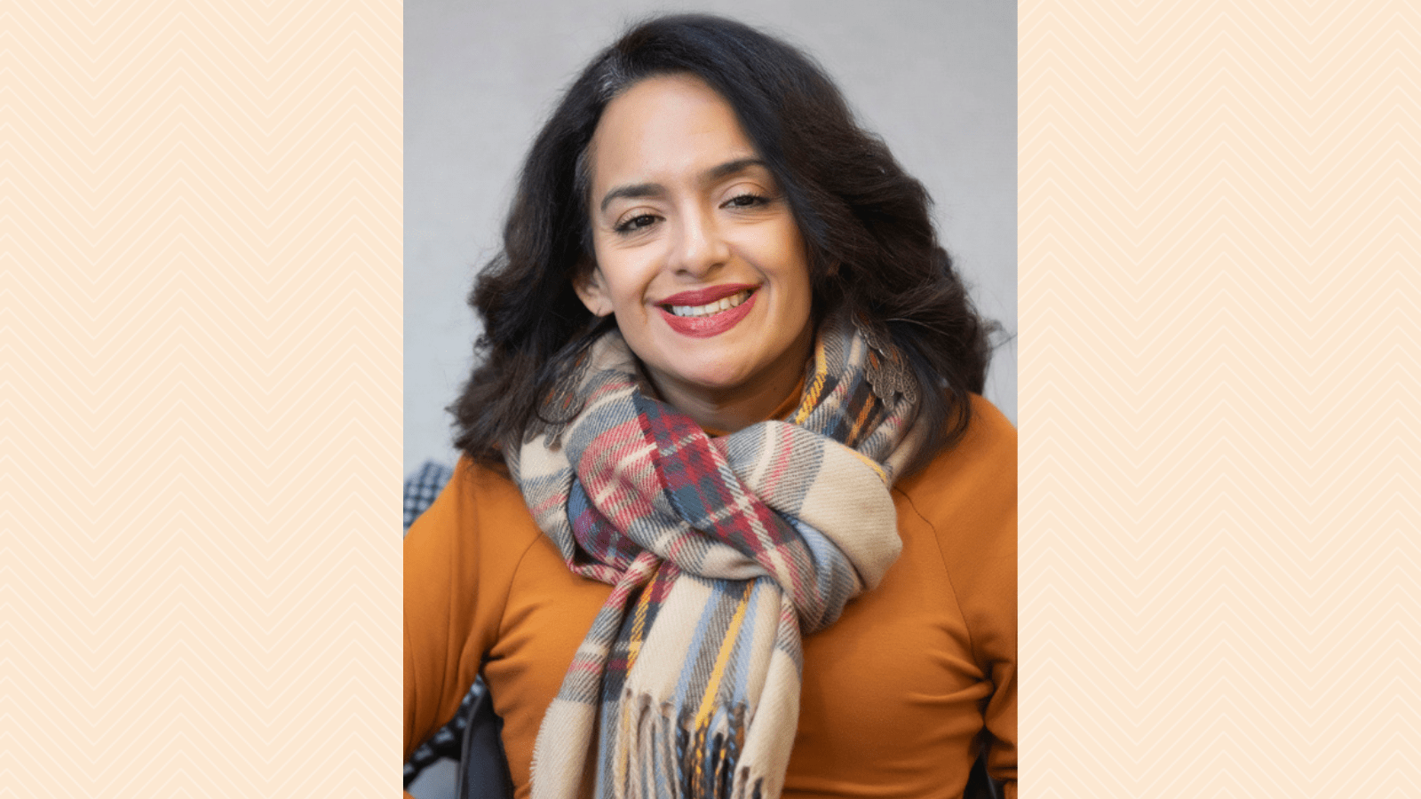 Graphic with a taupe background with a herringbone pattern featuring a photo of Ligia Andrade Zúñiga, a woman color with a disability smiling, she has long wavy hair, is wearing a scarf, and has long dangly earrings.
