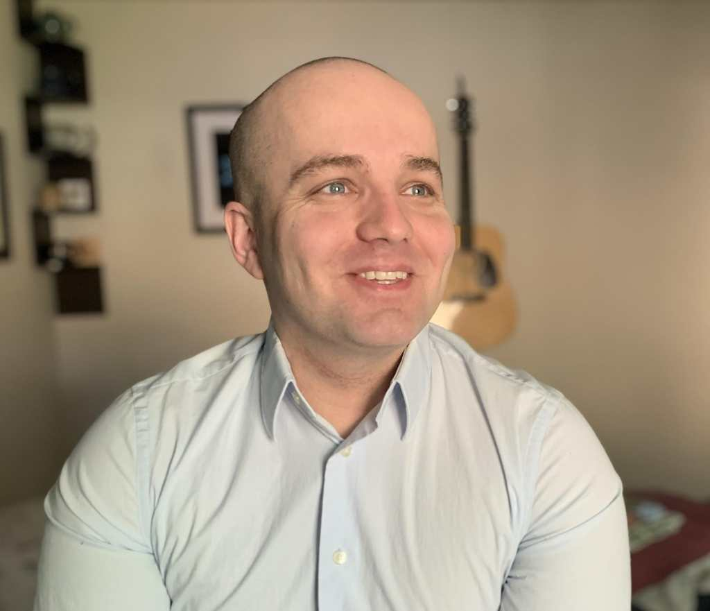 A photo of Jamison Hill, a young white man with an almost clean-shaven head with expressive blue eyes. He is looking away from the camera, slightly to the right and wearing a light blue, long-sleeved button down shirt. He is smiling.