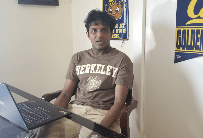 The image shows a young American male in his 20s of Indian American descent, with brown skin and black hair. He is sitting at a desk with a laptop open in front of him with some books on the side of the table. The laptop has the word Berkeley on it as does the brown t-shirt he is wearing. Behind him on the wall are college banners and posters with words like Cal, Golden Bears, and catchy phrases like, Bear Den, enter at your own risk.