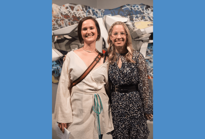 Graphic with a blue-gray background featuring a photo of curators Vanessa Chang and Lindsey D. Felt standing shoulder to shoulder in front of a graffiti installation, beaming at the camera. Lindsey has wavy blonde hair and wears translucent glasses and a gauzy black and white dress with a black double buckle belt. Vanessa has a short dark brown bob and wears a gold choker necklace and a long sleeved white kimono top. A brown bag strap crosses her chest.