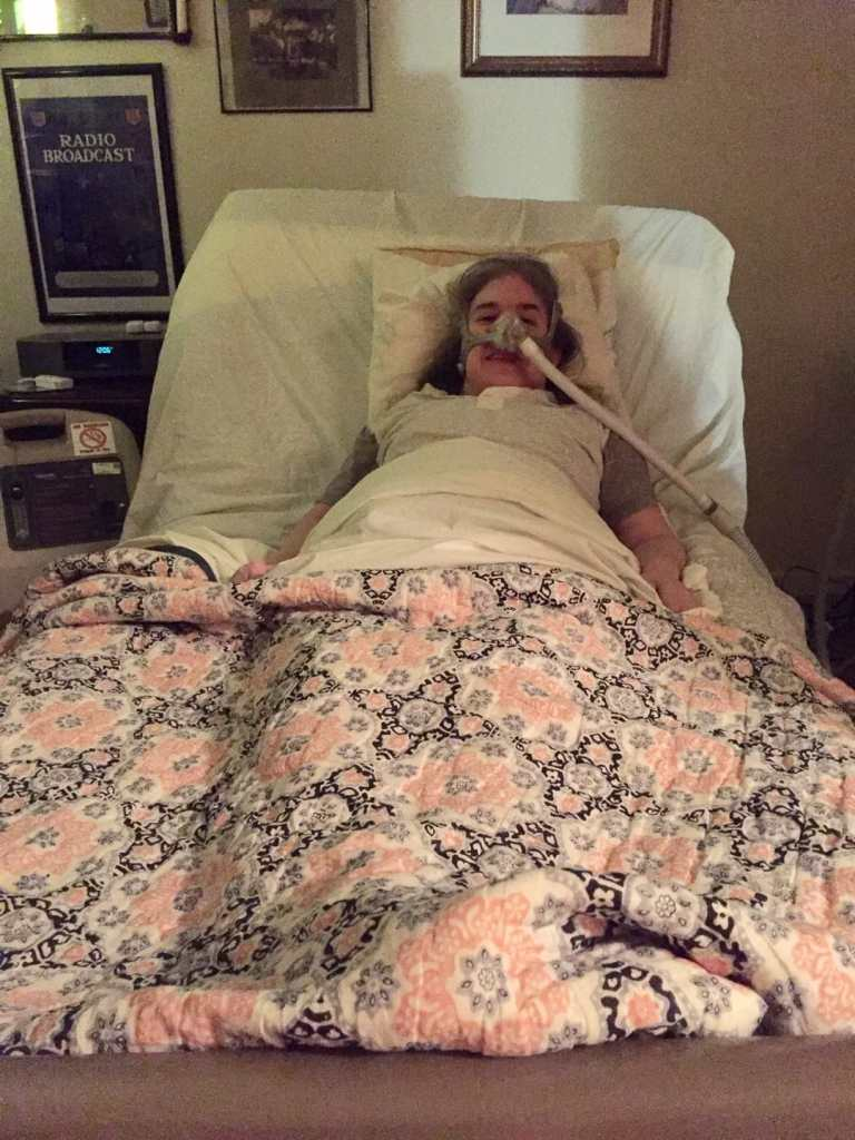 First day home from the hospital. Ingrid Tischer, middle-aged white woman wearing a Bi-Pap mask in a hospital bed under a colorful quilt.
